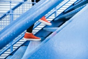 Feet in orange shoes walking up blue steps