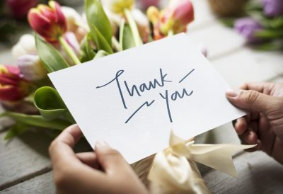 hands holding a thank you card with flowers in the background