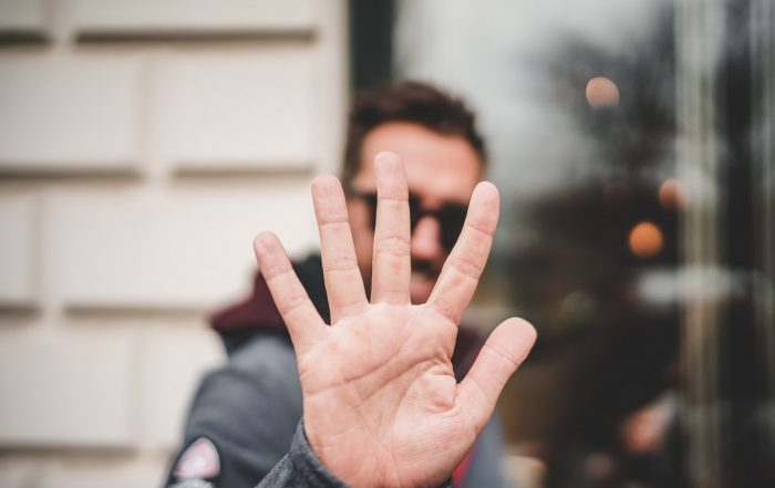 Man holding 5 fingers in front of his face
