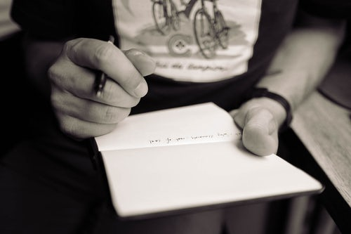 man with pen over blank page in a notebook