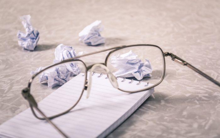 Writinf pad, eyeglasses, and waded sheets of paper