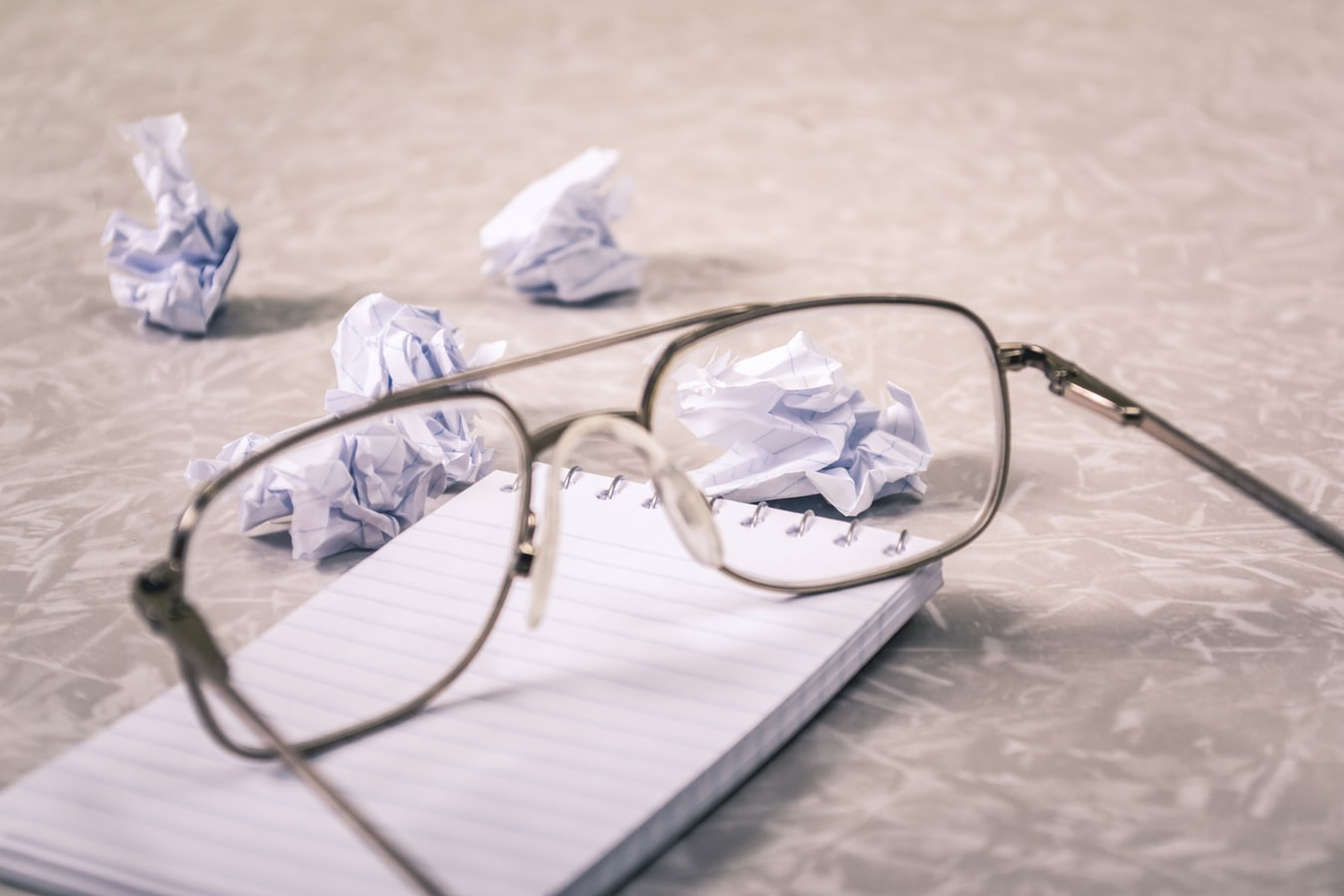 Writinf pad, eyeglasses, and waded sheets of paper