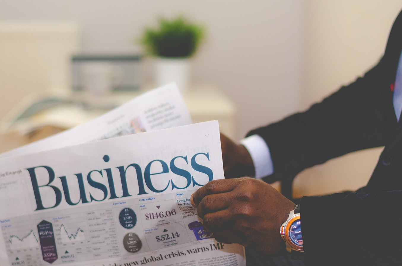 man in suit reading the business section of a newspaper