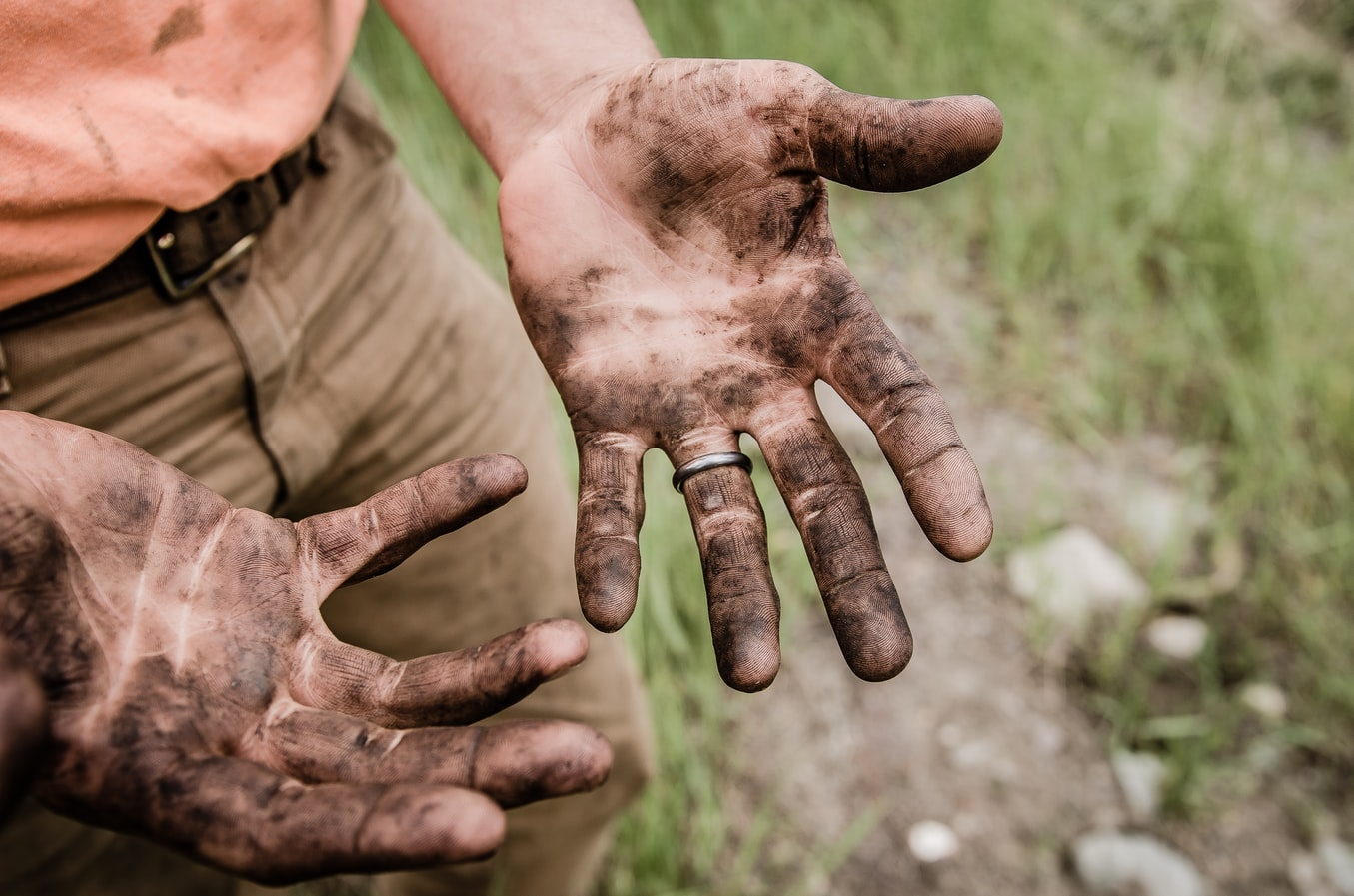 MUD COVERED HANDS OF WORKER