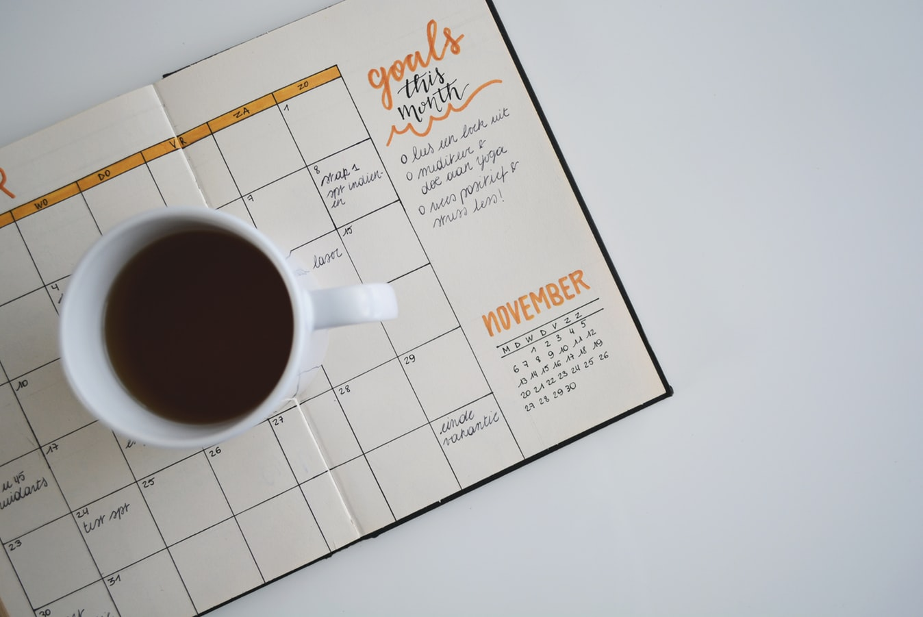 Cup of coffee on a calendar with monthly goals