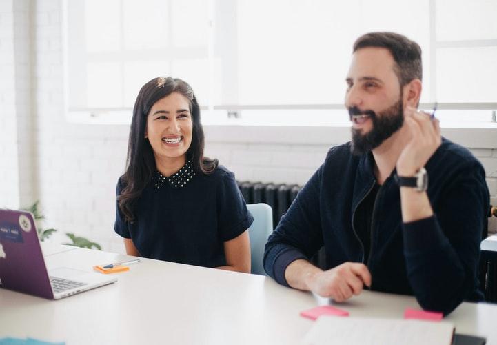 2 people at desk smiling