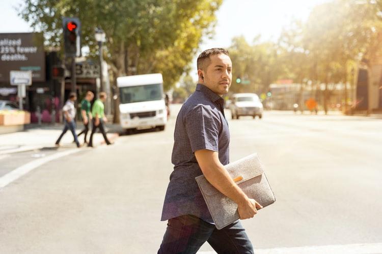 ,man crossing street with portfolio in hand