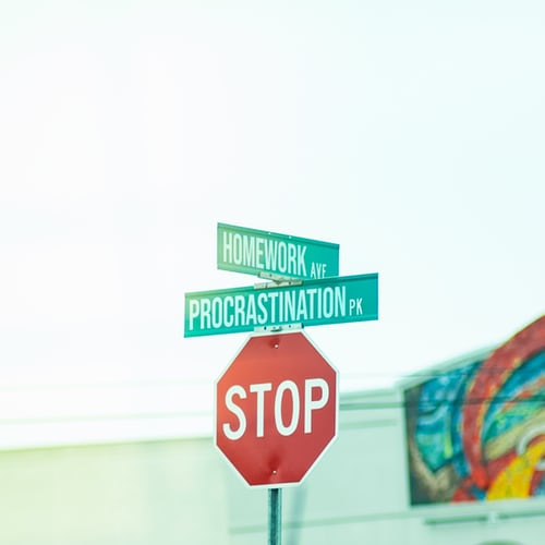 Stop sign with procrastination street sign