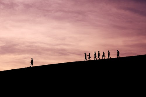leader on hill at sunset with a line of followers