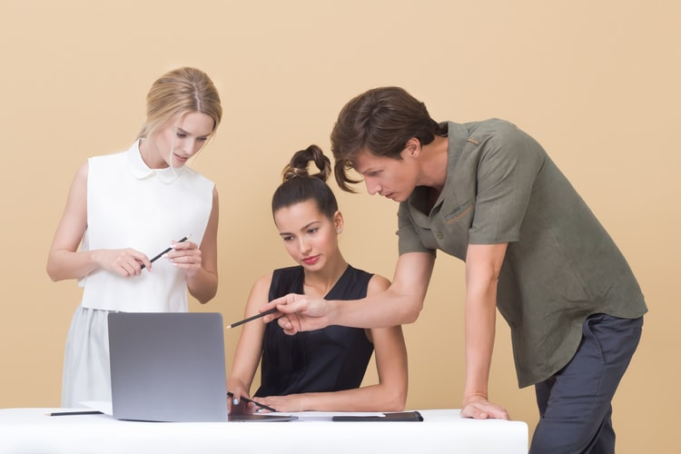 Three people pointing at computer screen i