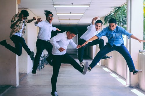 5 male co-workers jumping in the air simultaneously