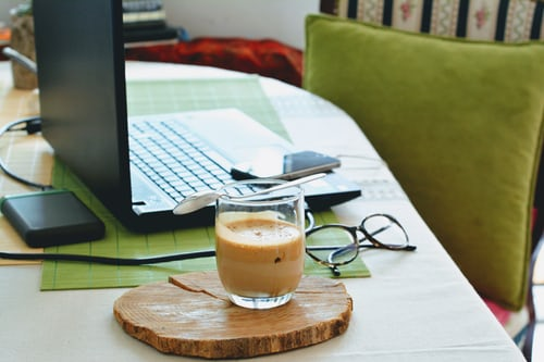 Laptop, phone, glasses, and beverage on table