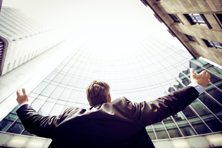 Man stnding in front of a sky scraper looking up with arms extended