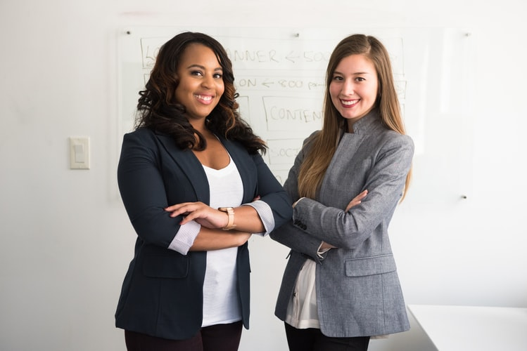 Two women standing in busines atire in fron of a white background