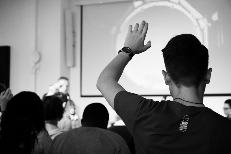 Man stading with raised hand to ask a question