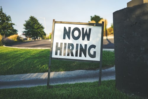 a now hiring yard sign in business park