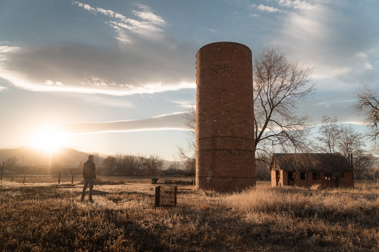Silo in a farm field at sunrise with person standing near to it