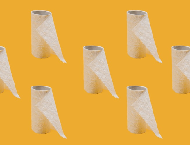 rolls of toilet paper against an orange background