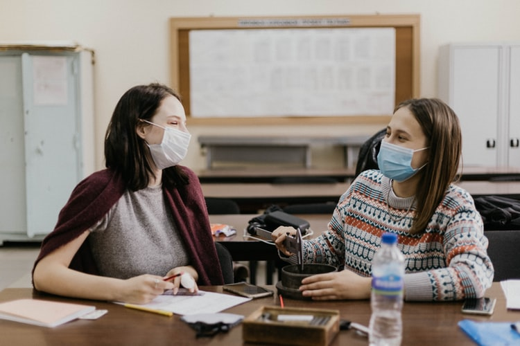 two women in masks at a work desk