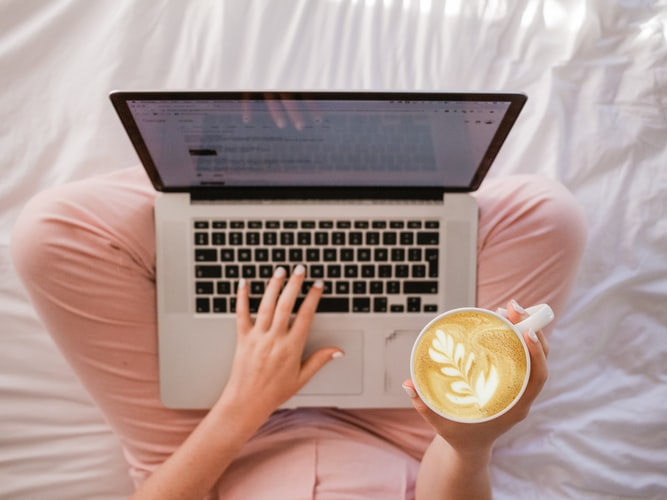 Person on bed with coffee looking at computer screen