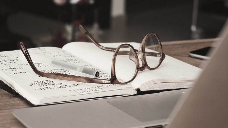 Eye glasses on papers on table
