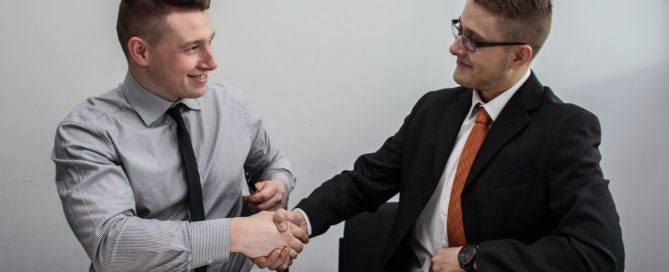 Two business people at table shaking hands
