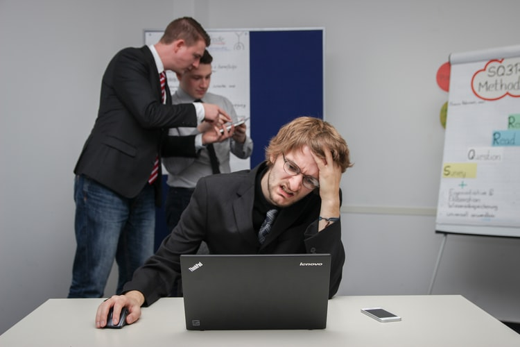 Mna holding his head in anguish looking at laptop