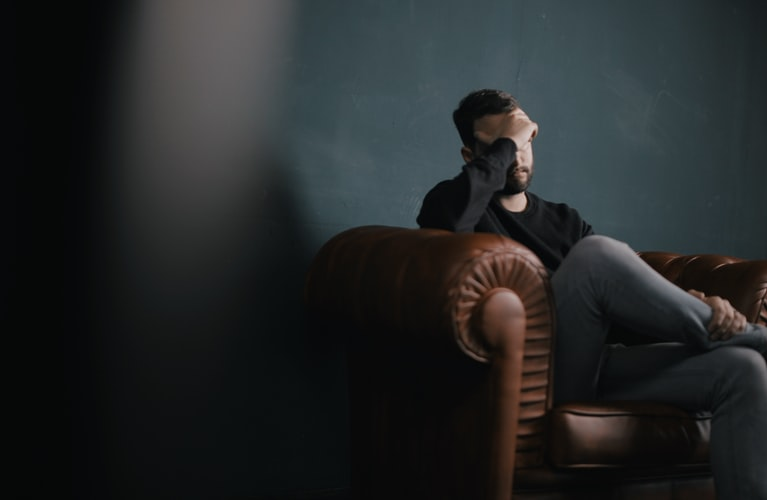 a aman holds his head while sitting on a couch