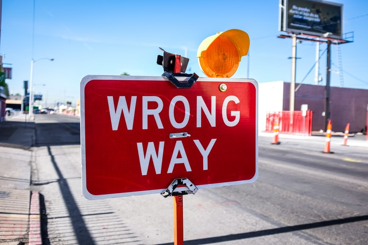 wrong way street sign with hard hat